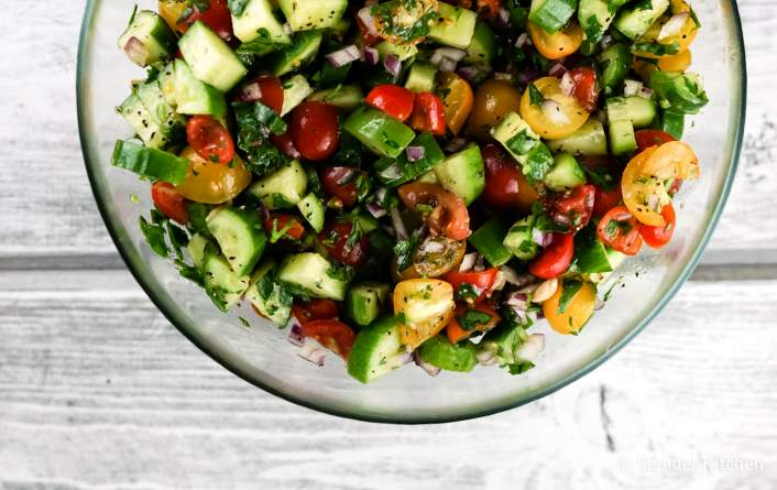 Israel Salad with chopped cucumber, tomato, onions, and herbs.