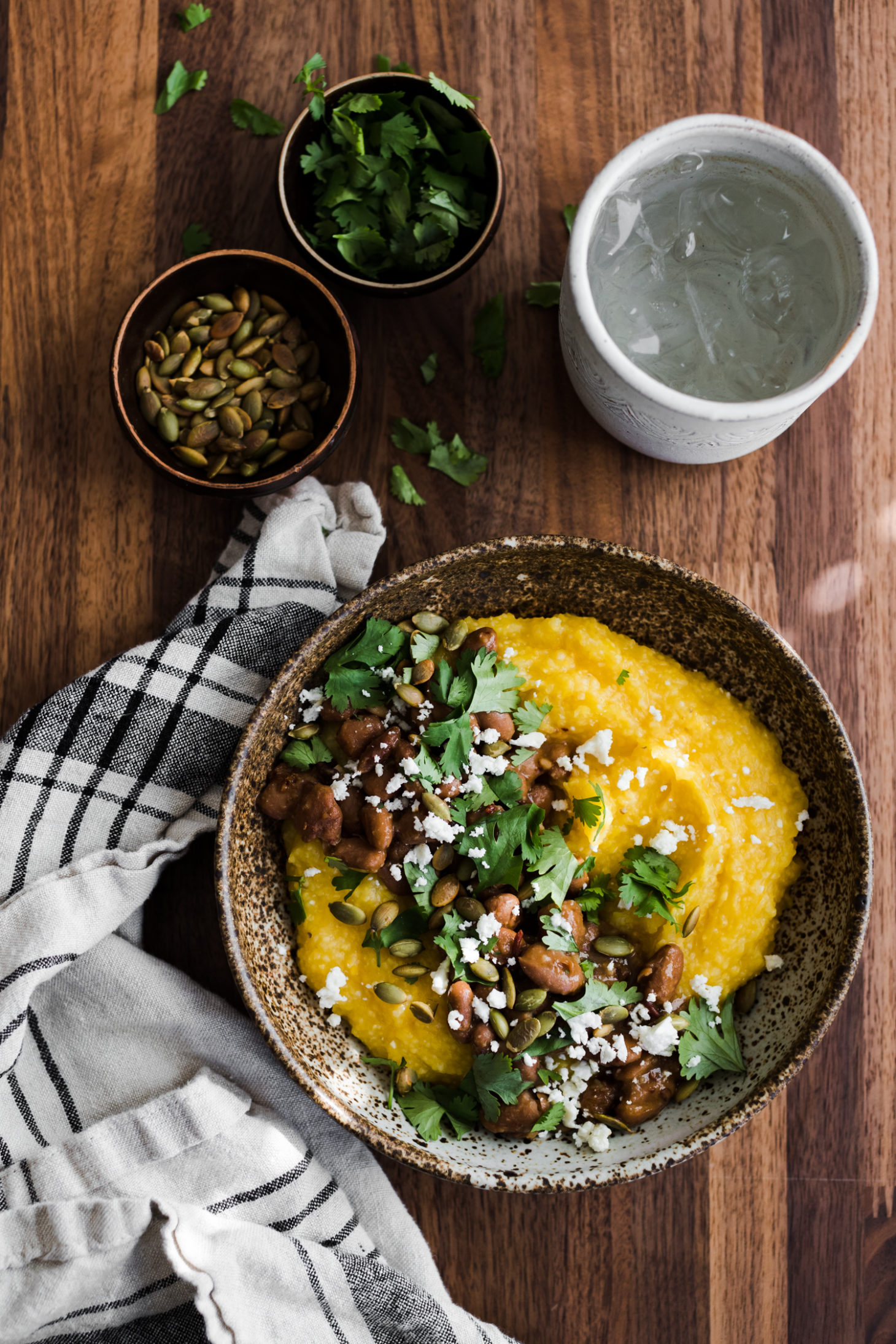 A vivid image of the pumpkin polenta is recorded with pinto, pepitas, and feta beans.